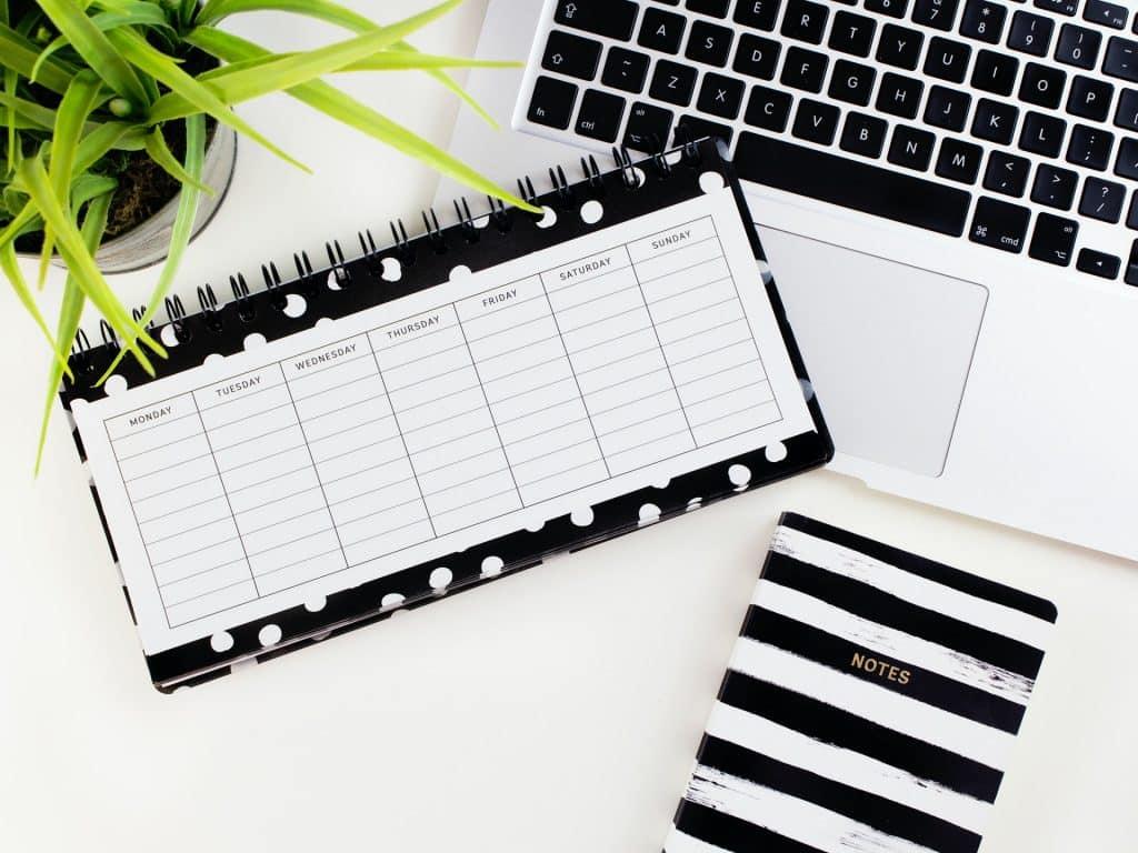 Planner preto e branco sobre mesa e notebook branco.
