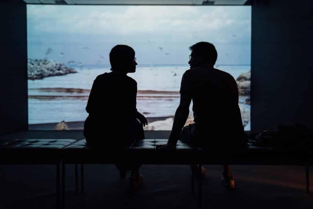 Silhuetas de duas pessoas sentadas num banco conversando.