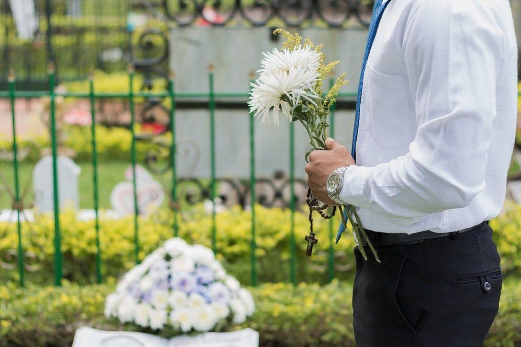 Imagem de um homem usando camisa branca e calça social preta. Ele está no cemitério no velório de um ente querido. Em suas mãos ele segura um ramalhete de flores brancas e amarelas e um terço.