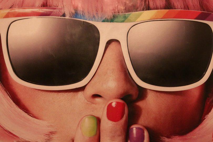 Imagem do rosto de uma mulher usando óculos de sol. Ela usa uma peruca rosa e as suas unhas estão pintadas de cores diferentes.