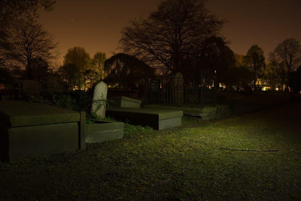 Imagem de um cemitério à noite. Várias lápides e muitas árvores compõem o cenário.
