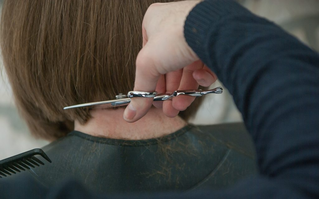 Imagem de uma mulher cortando bem curtinho o seu cabelo.