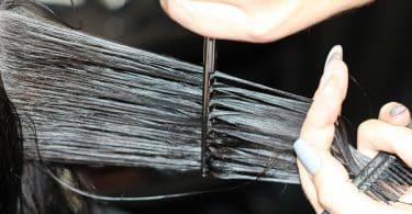 Imagem de uma mulher de cabelos longos e pretos cortando o cabelo.