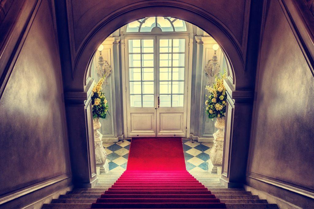 Imagem do hall de entrada de uma casa. Ao lado da porta dois vasos grandes de mármore com rosas-amarelas. Na porta até as escadas um tapete vermelho forra o piso.