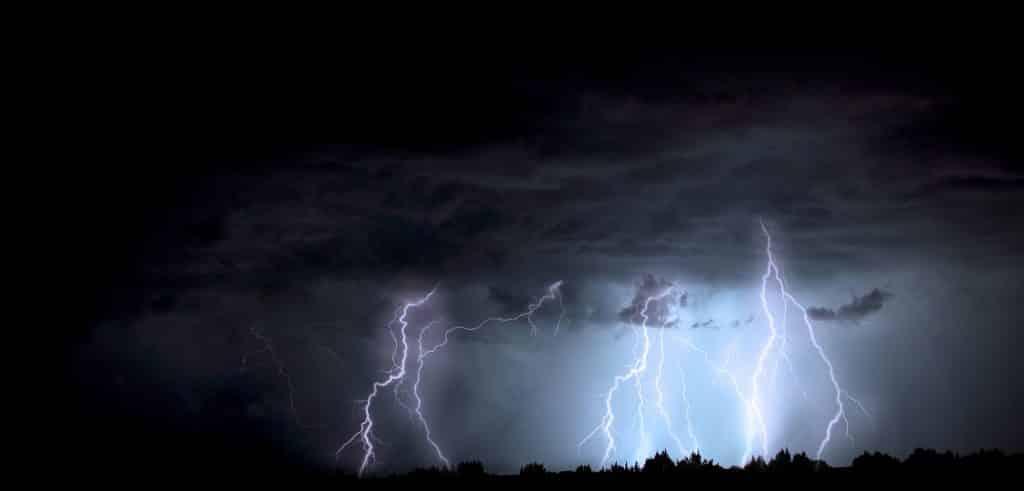 Imagem de muitas nuvens escuras no céu e entre elas muitos raios anunciando uma tempestade.