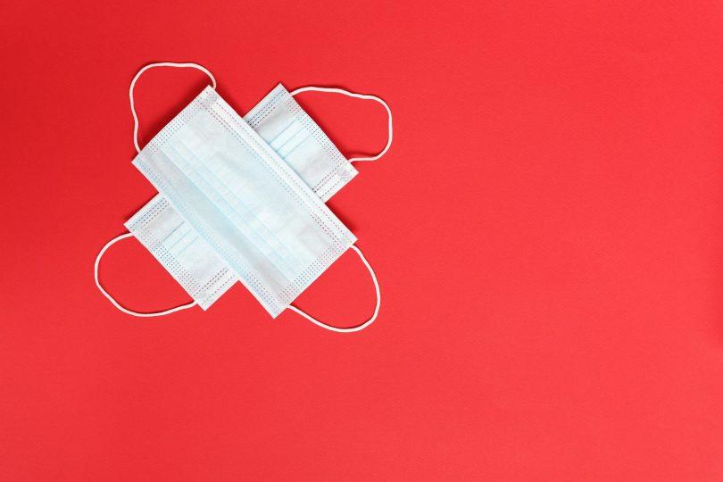 Imagem de fundo vermelho e sobre ela duas máscaras de proteção facial contra a Covid-19. Elas estão dispostas uma sobre a outra.