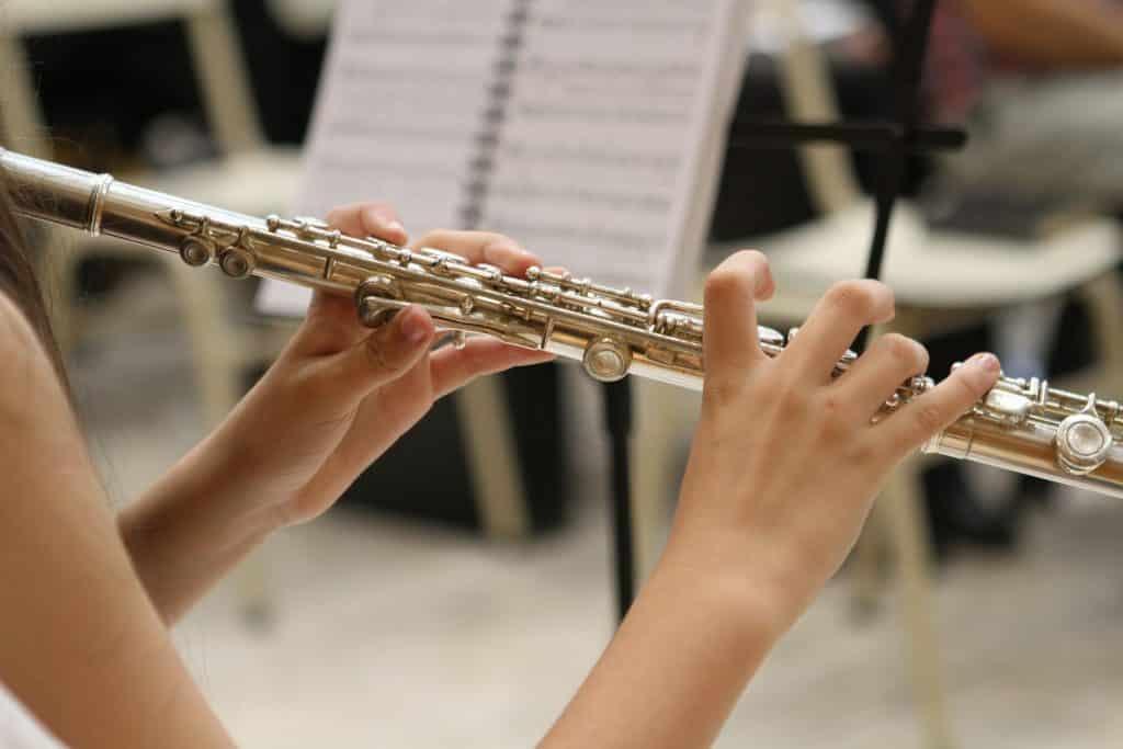 Imagem de uma moça sentada tocando uma flauta na cor dourada.