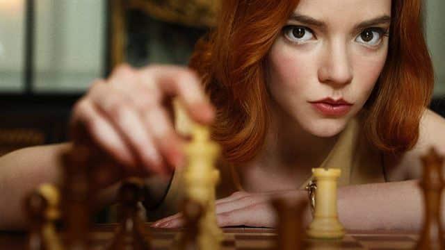Mulher ruiva jogando xadrez.