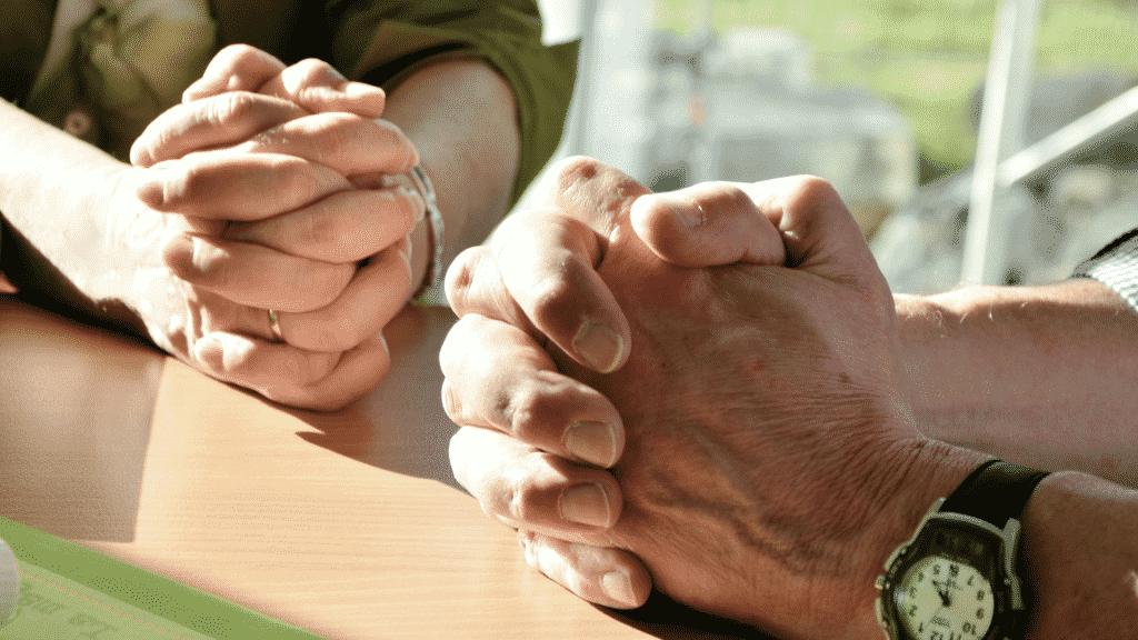 Mãos de pessoas orando sobre a mesa