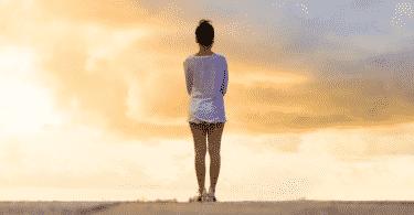 Silheta de mulher olhando para o pôr do sol