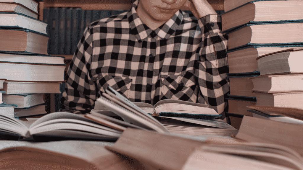 Pessoa lendo livro com pilhas de livros ao seu redor