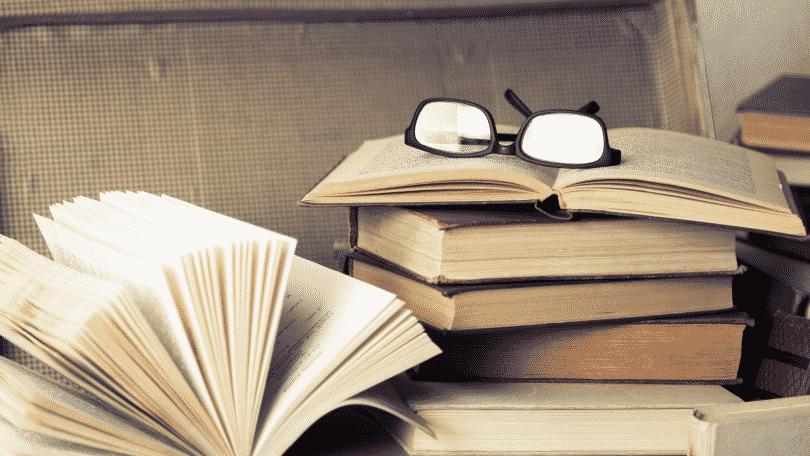 Pilha de livros com óculos acima de livro aberto