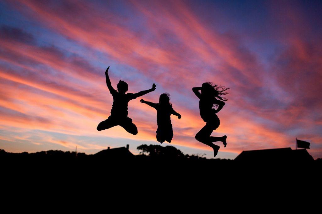 Imagem do céu e o por do sol à frente dele três pessoas amigas saltando.