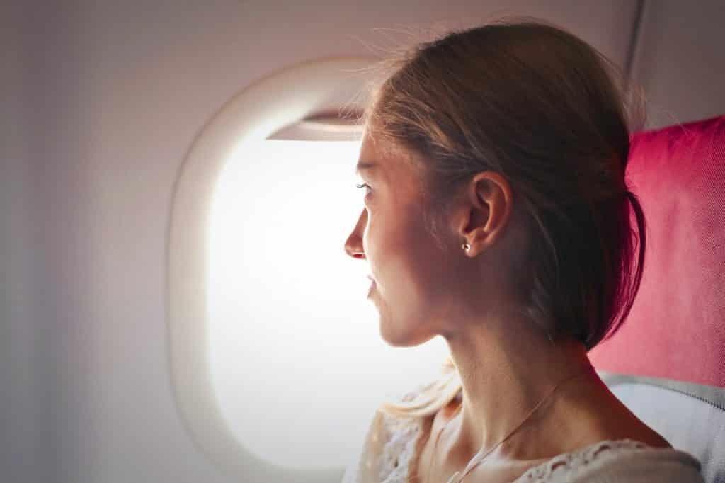 Menina loira dentro do avião olhando pela janela