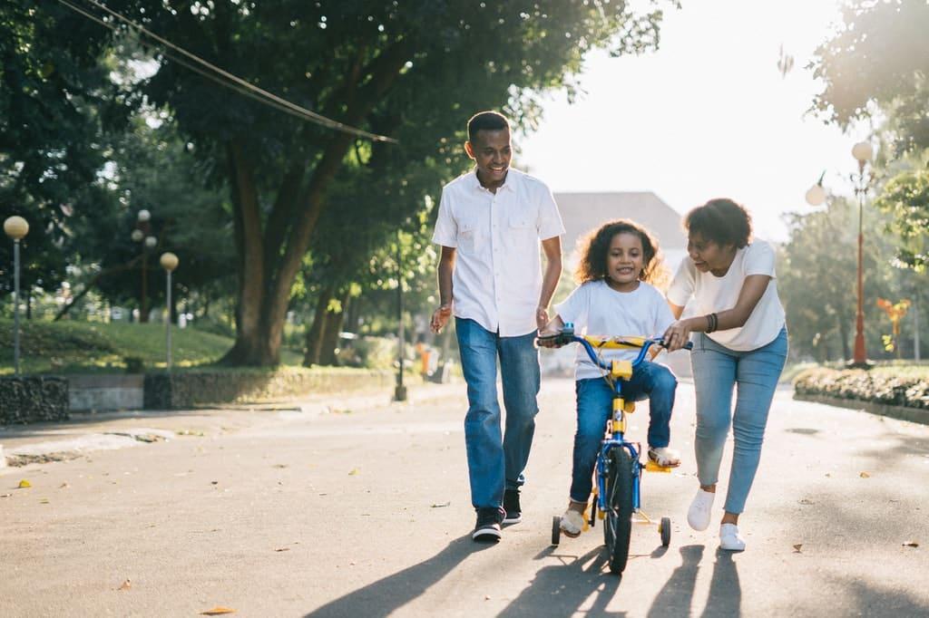 Pais ensinam filha a andar de bicicleta.