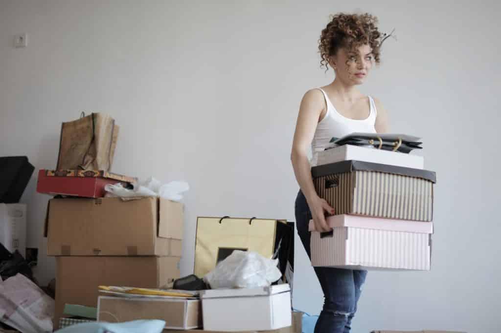 Mulher segurando caixas com mais caixas ao fundo representando organização
