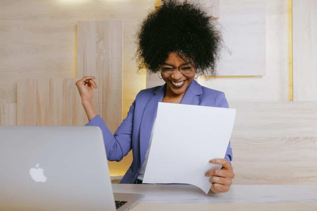 Mulher negra segurando uma folha branca enquanto comemora uma conquista, sentada com o notebook aberto logo a frente.