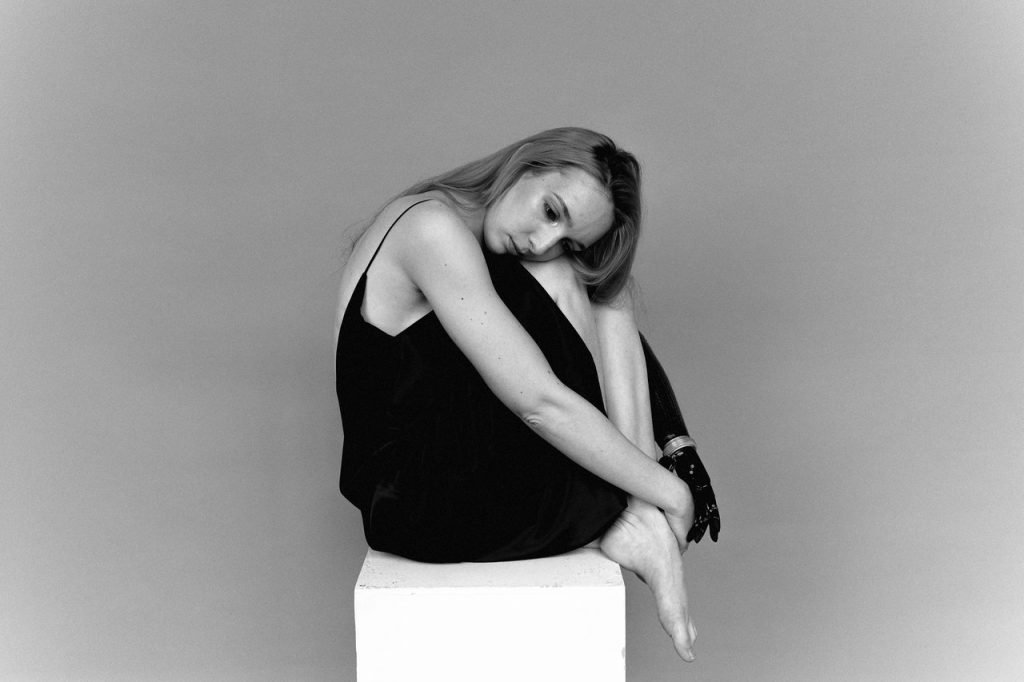 Menina frustrada sentada com um vestido preto e apoiando a cabeça nas pernas