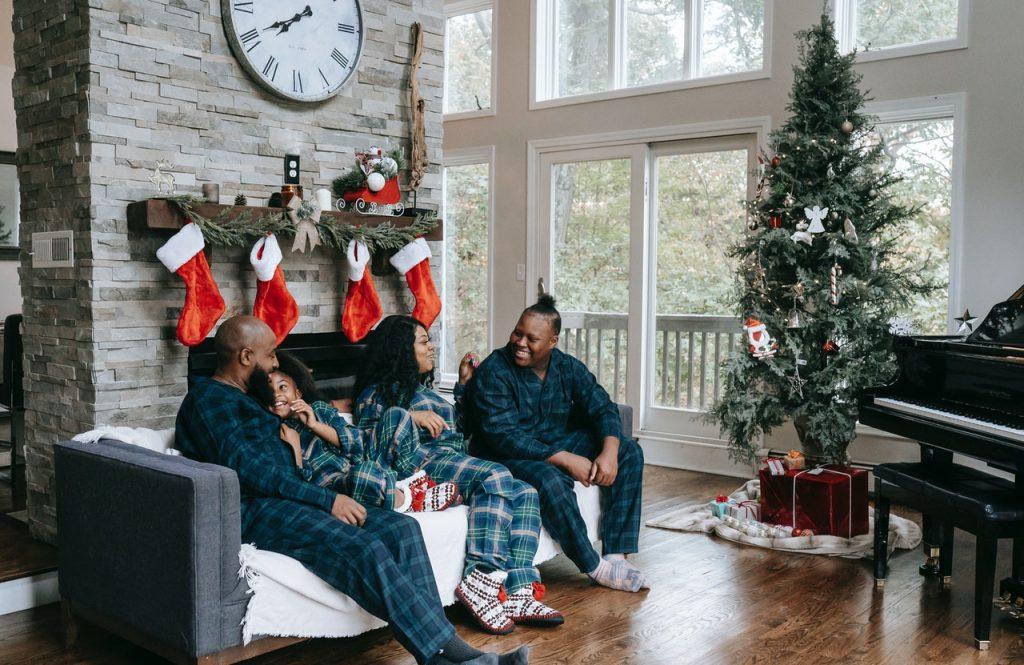 Família conversando sentados no sofá ao lado da árvore de natal