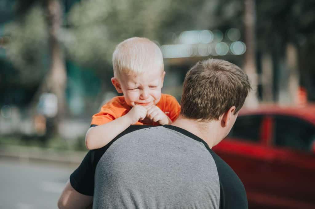 Homem adulto segura criança que está chorando.