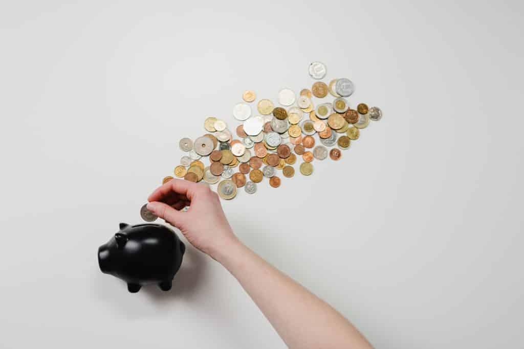 Pessoa colocando moedas em um porquinho de cofre