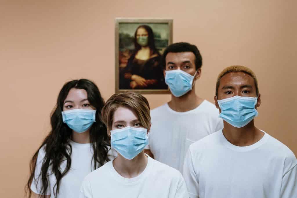 Duas mulheres e dois homens com máscaras.