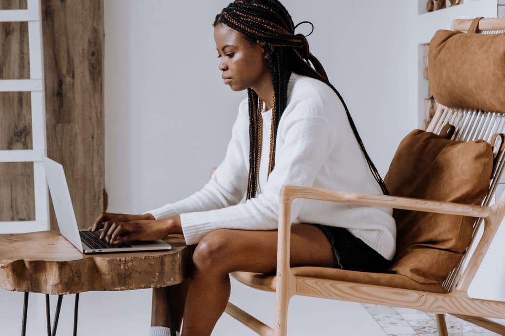 Mulher sentada em cadeira enquanto digita em um computador.