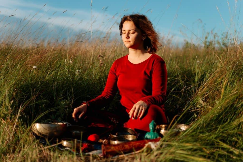 Mulher sentada na grama. Em sua frente há alguns objetos diversos e uma estátua de Buda.