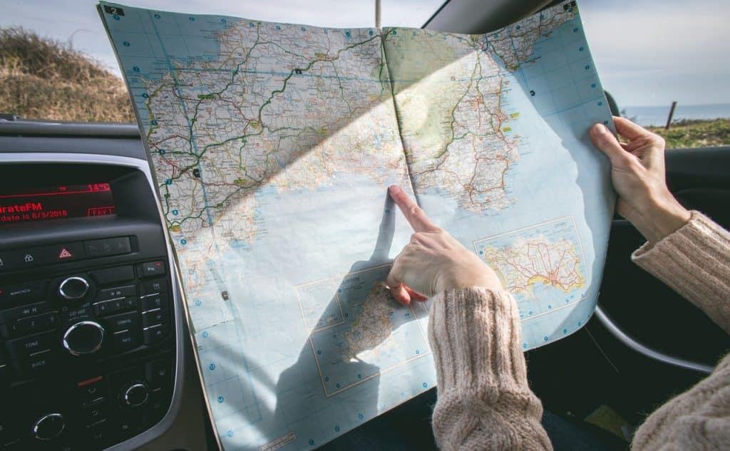 Menina apontando para um mapa dentro do carro
