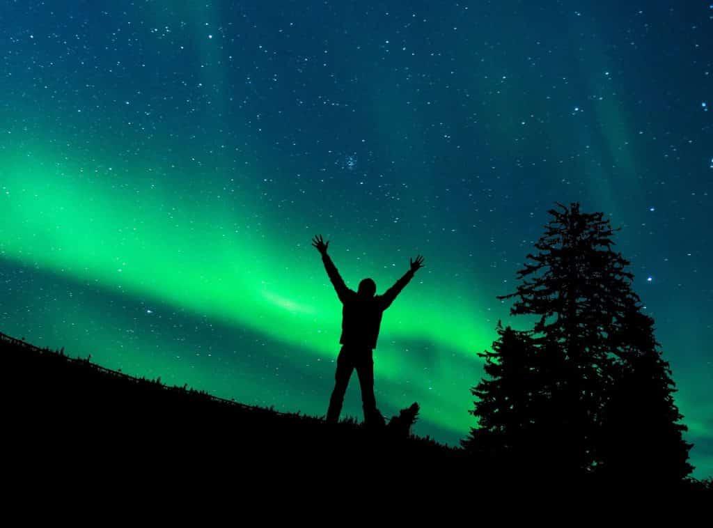 Silhueta de um homem com os braços abertos. Atrás dele está uma aurora boreal.