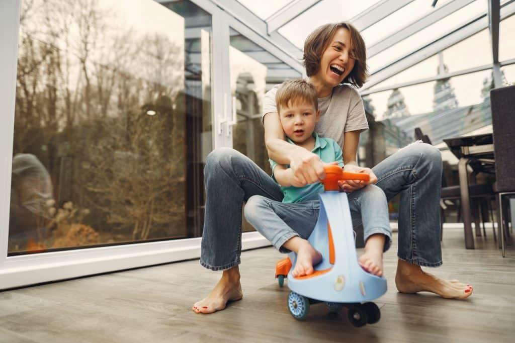 Mulher adulta brinca com criança em cima de brinquedo móvel.