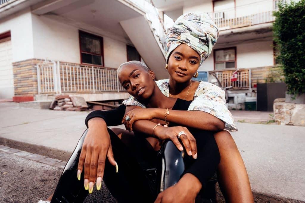 Duas mulheres sentadas na calçada se abraçam.