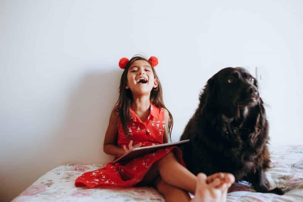Menina ao lado de um cachorro preto. Ela está sorridente e segura um tablet nas mãos.