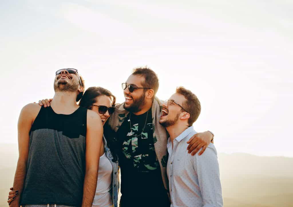 Quatro amigos se abraçando enquanto estão rindo