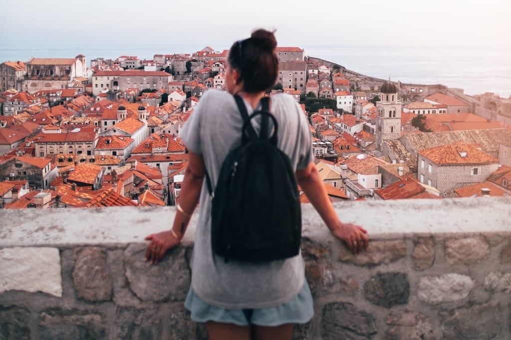 Mulher observa, de um ponto alto, uma cidade.
