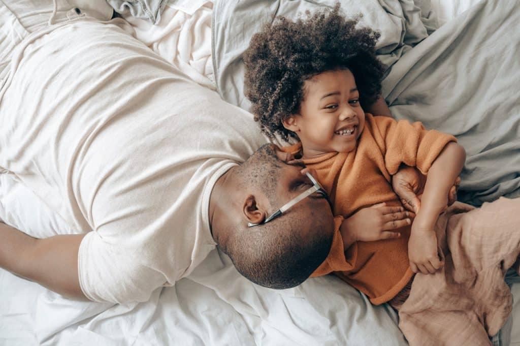 Pai e filho deitados na cama brincando