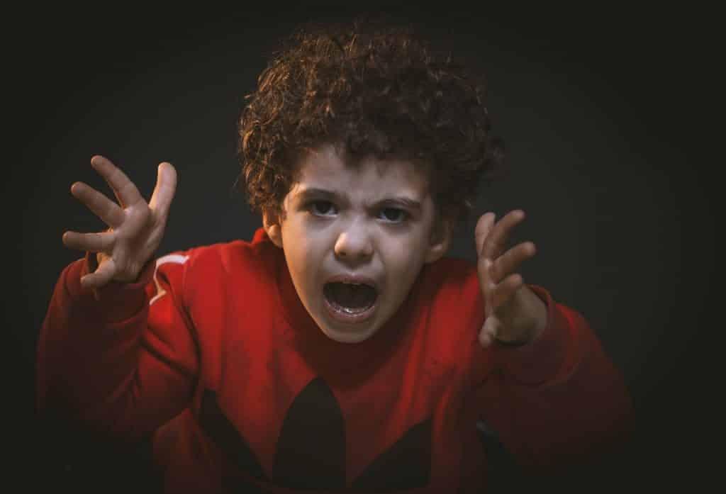 Criança gritando com as mãos erguidas.