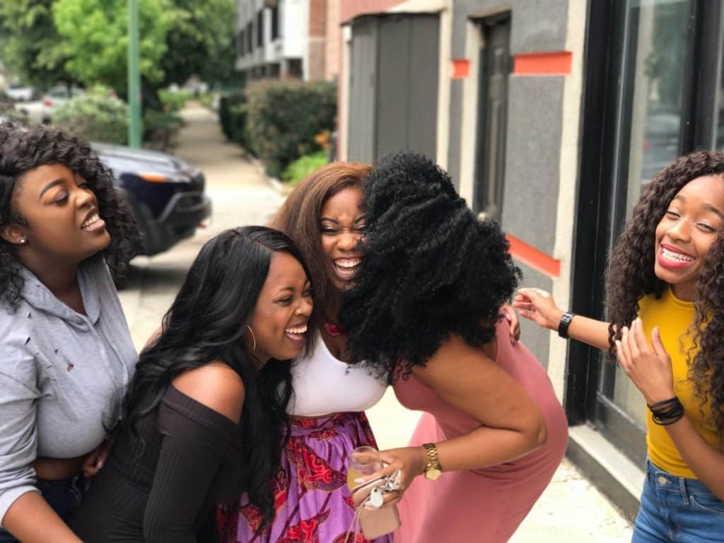 Grupo de cinco amigas rindo na rua