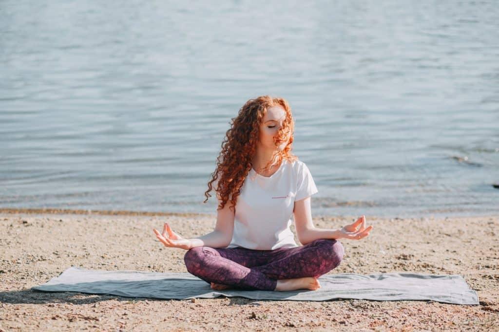 Mulher sentada em posição de meditação em uma praia.