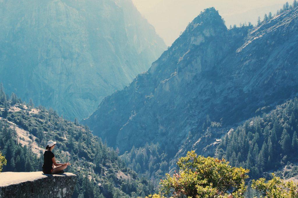 mulher meditando enquanto observa a natureza