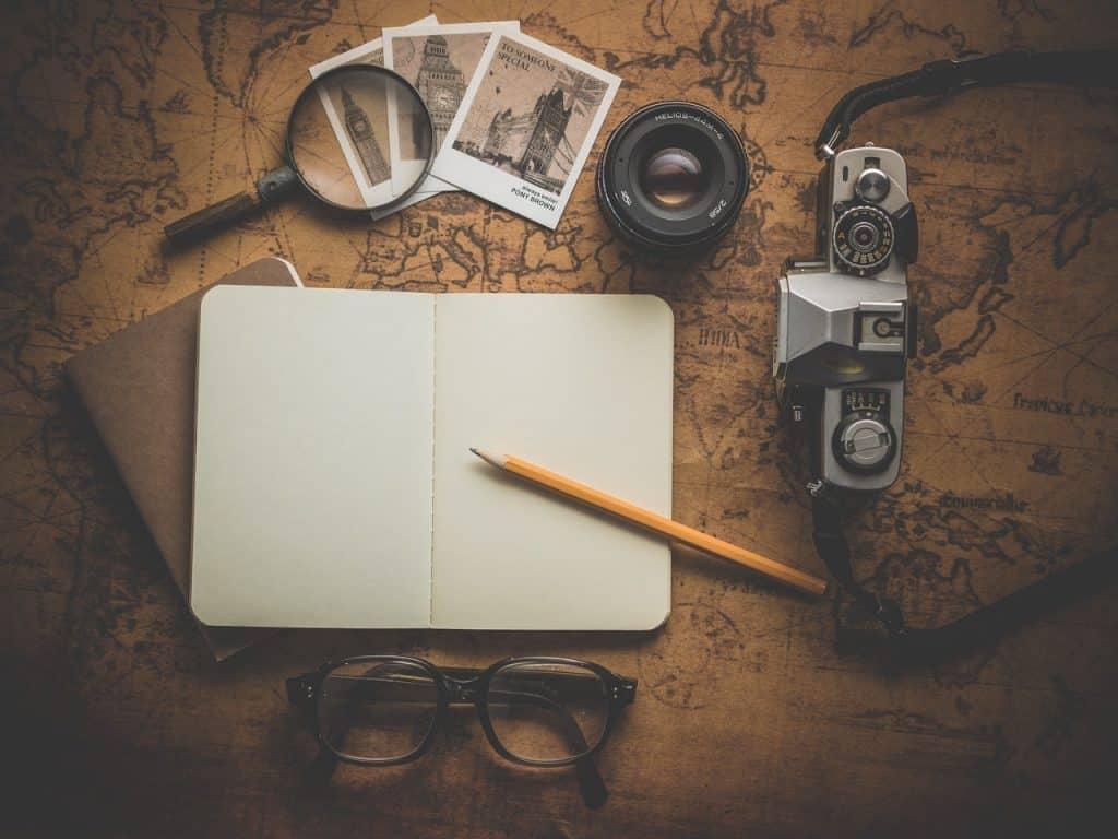 Um caderno em branco, fotografias, uma lupa, óculos e uma câmera fotográfica em cima de uma mesa de madeira