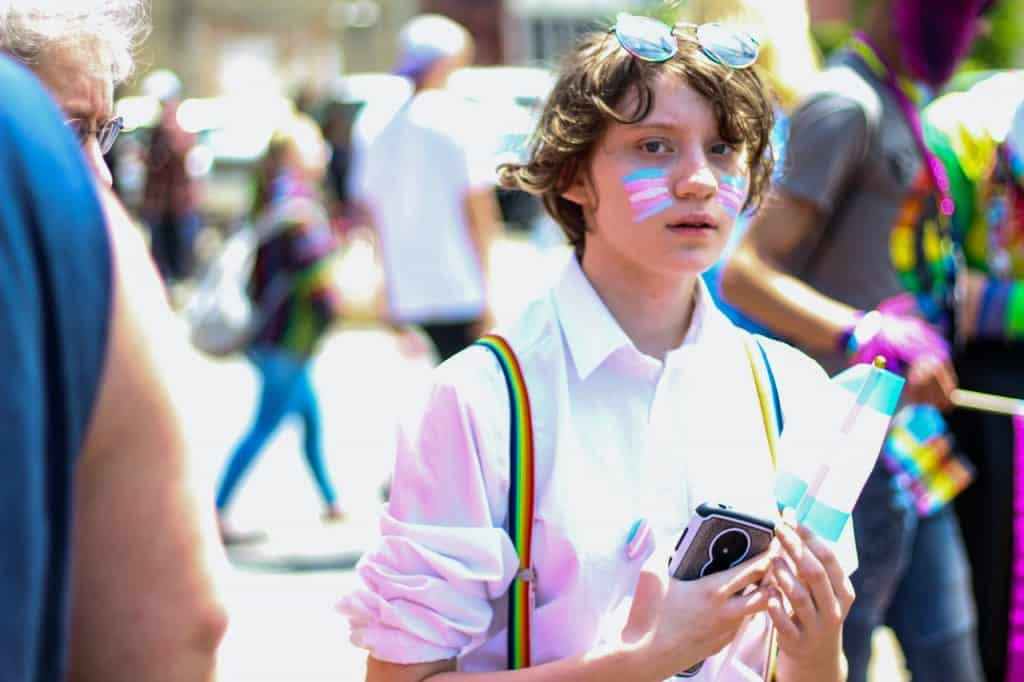 Menino branco com pintura da bandeira transexual no rosto.