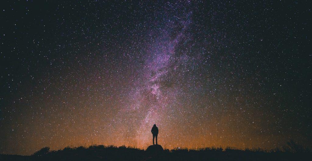 Silhueta de uma pessoa em um campo aberto com um céu estrelado ao fundo.