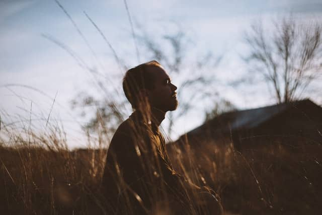 Homem branco sentado num campo com os olhos fechados.