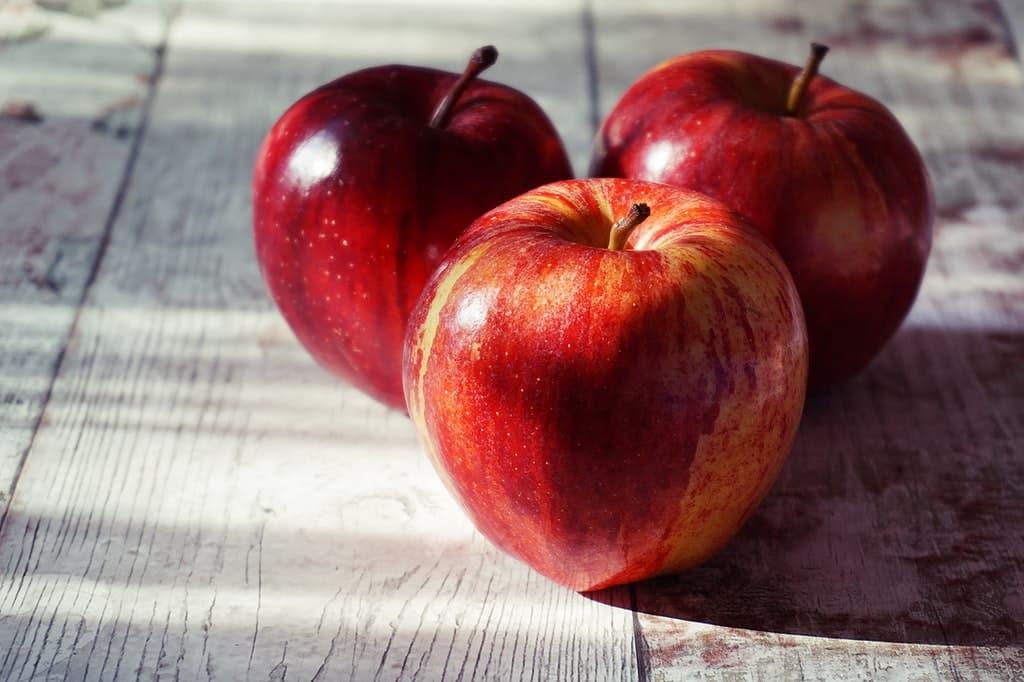Três maçãs vermelhas dispostas sobre mesa.