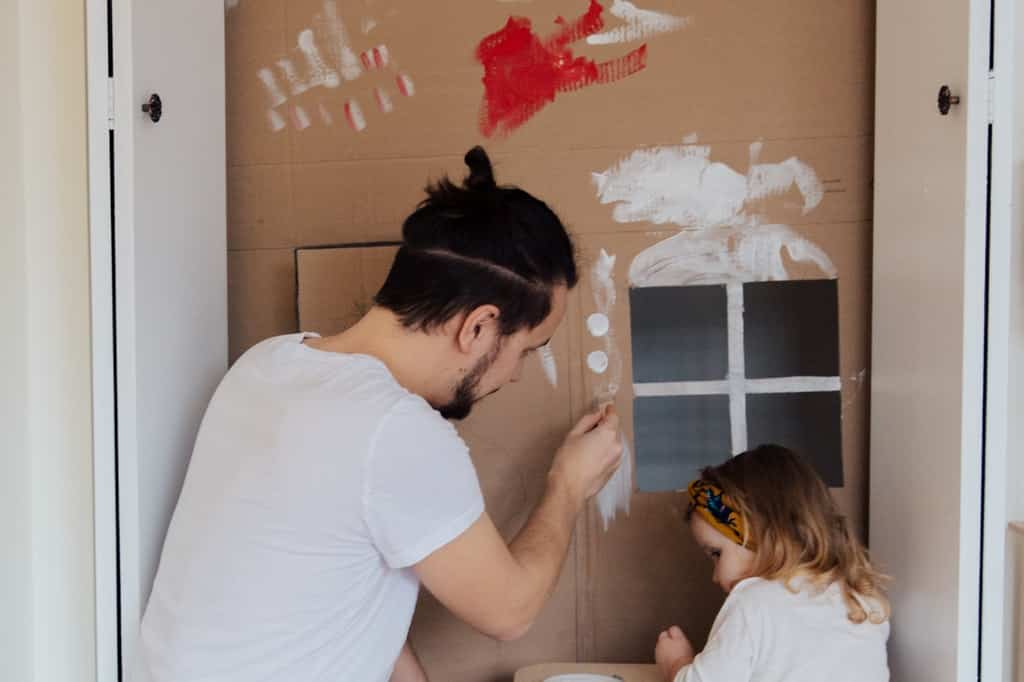 Homem adulto e menina pintam papelão.
