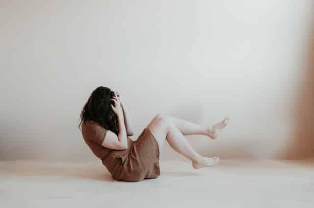 Mulher branca sentada no chão com pernas levantadas e braços no rosto.
