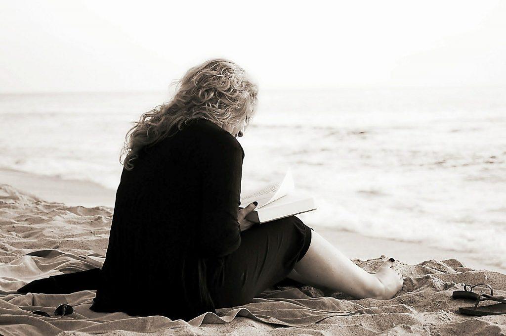 Imagem em preto e branco de uma mulher usando um vestido longo na cor preto. Ela está sentada na areia de frente para o mar lendo a bíblia.