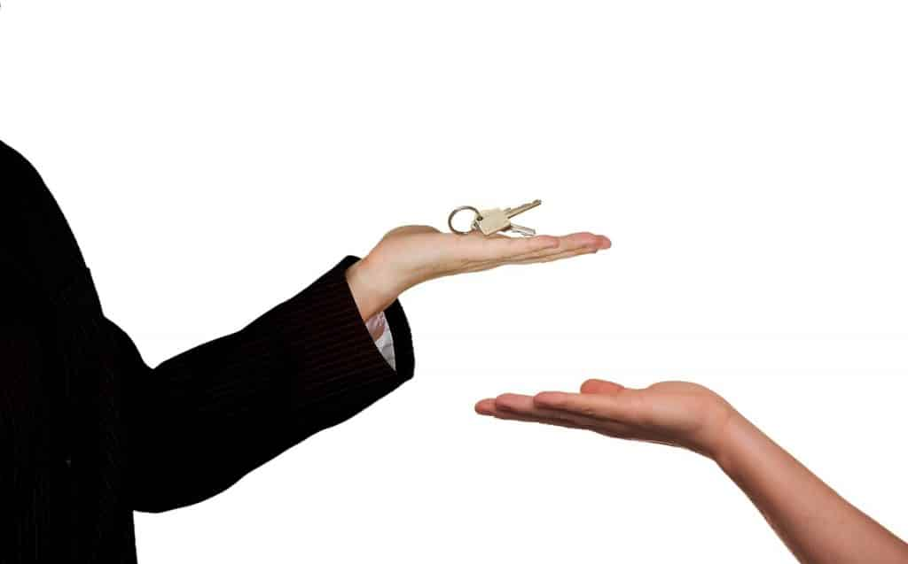 Imagem de uma pessoa usando um terno preto entregando uma chave nas mãos de uma outra pessoa.