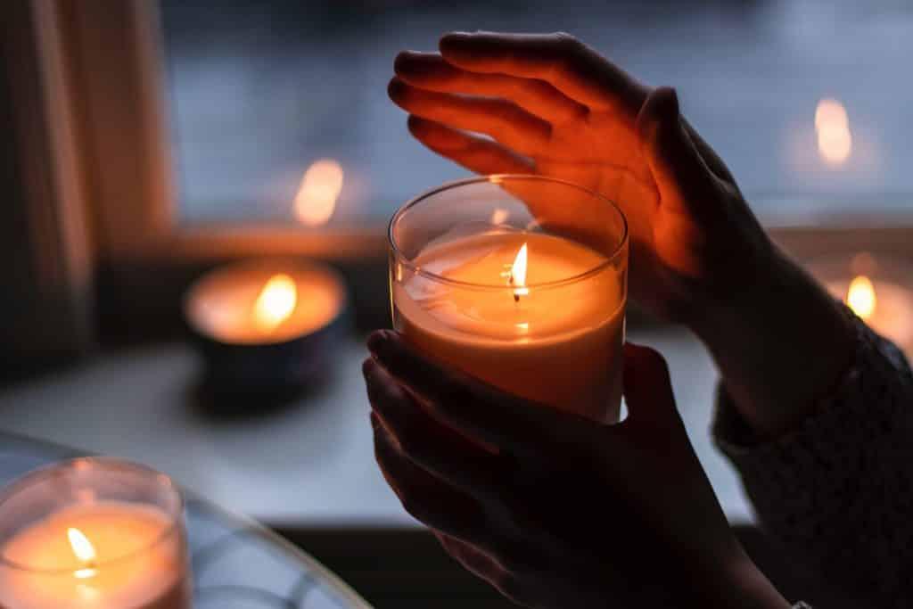 Mãos femininas brancas segurando vela acesa.